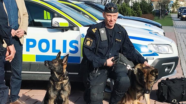 Niklas Kjellman står på knä mellan två schäfrar. Han har på sig polisuniform  och mössa 193002e064f53