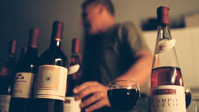 En man bakom ett bord fullt av vinflaskor