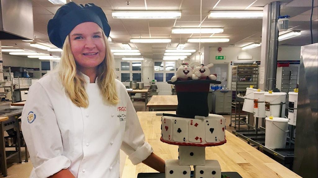 Josefine Pagander står iklätt bagare-kläder bredvid den tårta som hon har bakat.