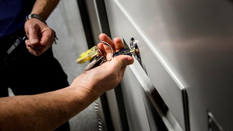 En häktesvakt använder nycklar för att öppna en celldörr.