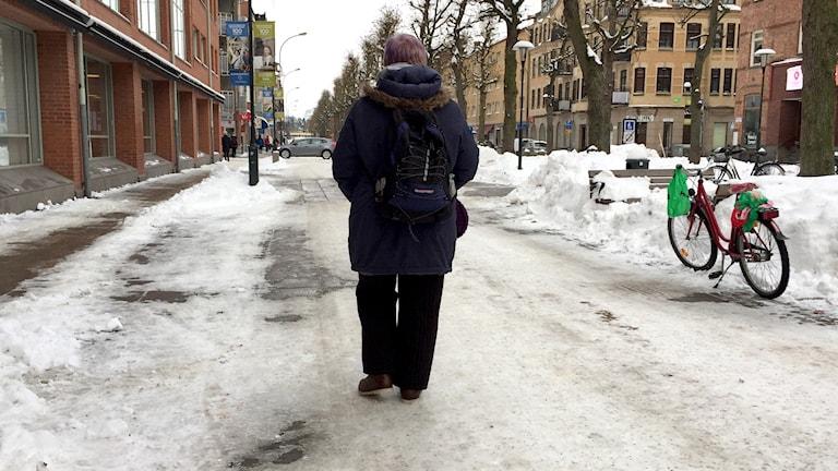 Ryggen på en kvinna som går bortåt på en snöig gågata. Foto: Lars Sergård/Sveriges Radio