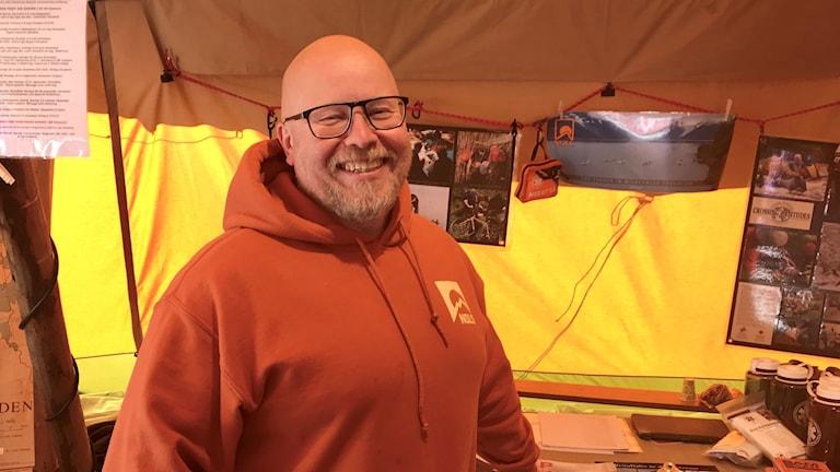 Porträtt av en nöjd Jonas Alexandersson i en jättestor tipi. Ute skiner solen. Jonas har orange hoodie, snaggat hår och svarta glasögon.