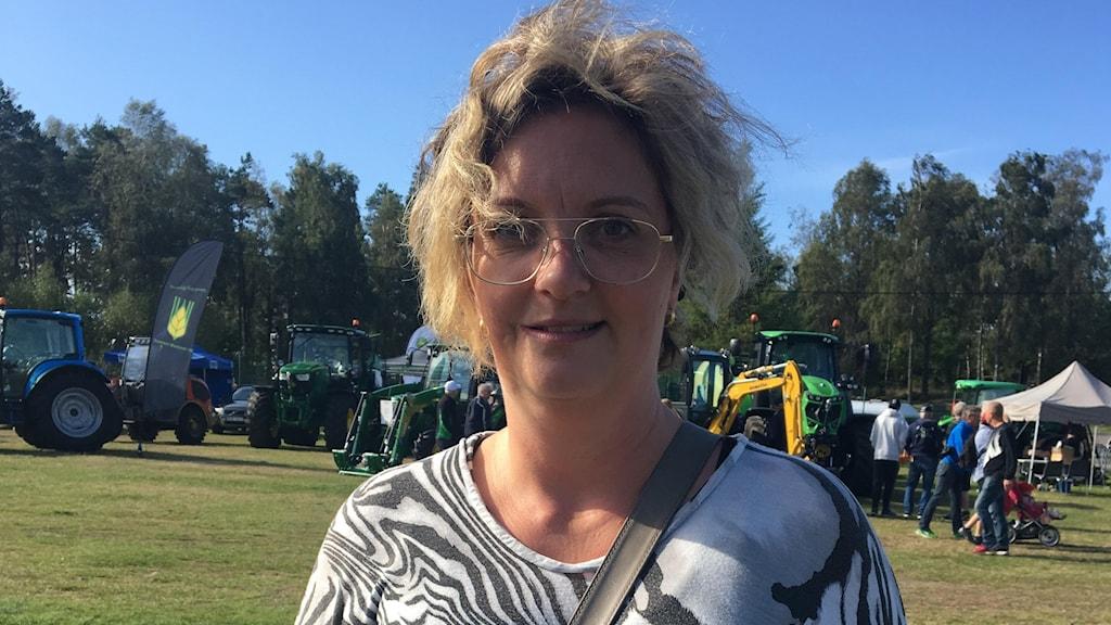 Susanne Blom Ottosson står framför traktorer, det blåser i hennes hår