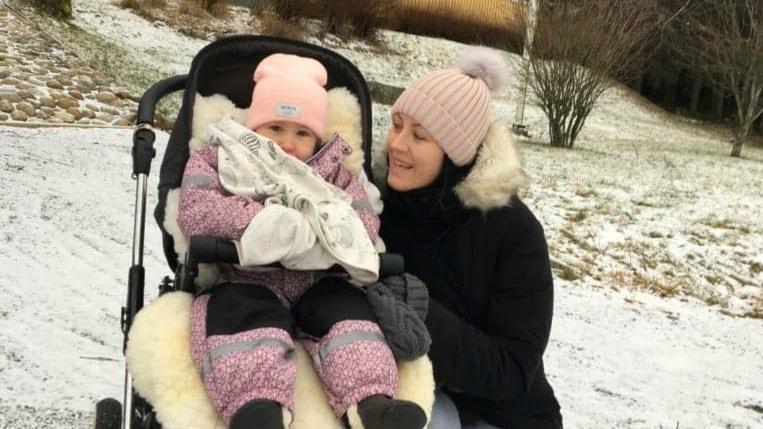 Molly och Emma Tervo som sitter i snön och ser glada ut. Molly sitter i sin rullstol.