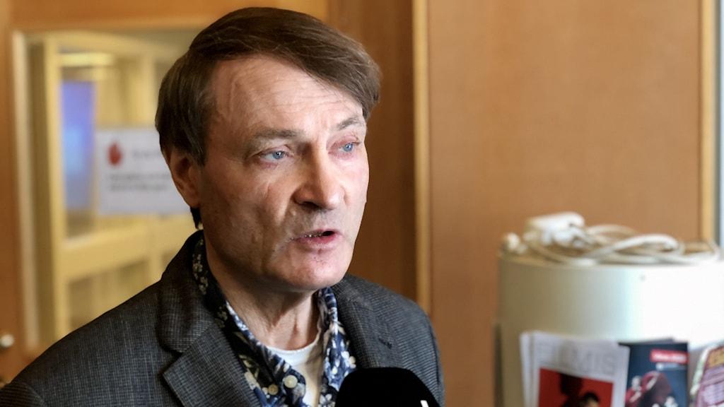 Mikael Staxäng, moderaternas gruppledare i Uddevalla. Han har brunt, kammat hår. Ganska blekt anlete. Grå kostym och en blå/vit-färgad skjorta med blommotiv (verkar det som). Han står i kommunhusets foajé i Uddevalla.