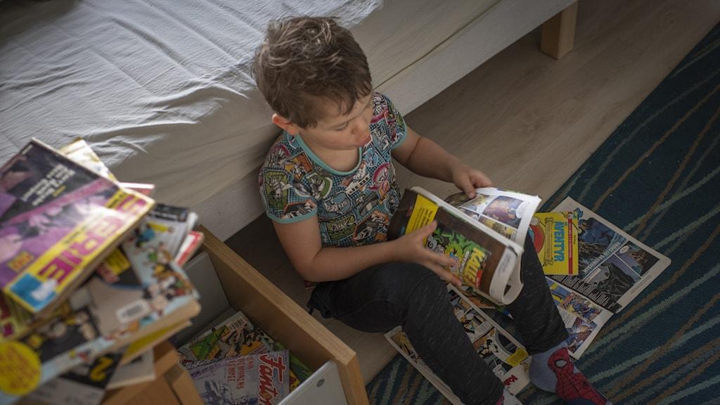 Pojke som läser serietidning.