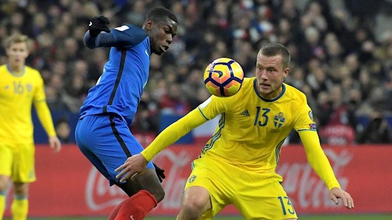 Jakob Johansson i duell med Paul Pogba vid en landskamp mellan Sverige och Frankrike.