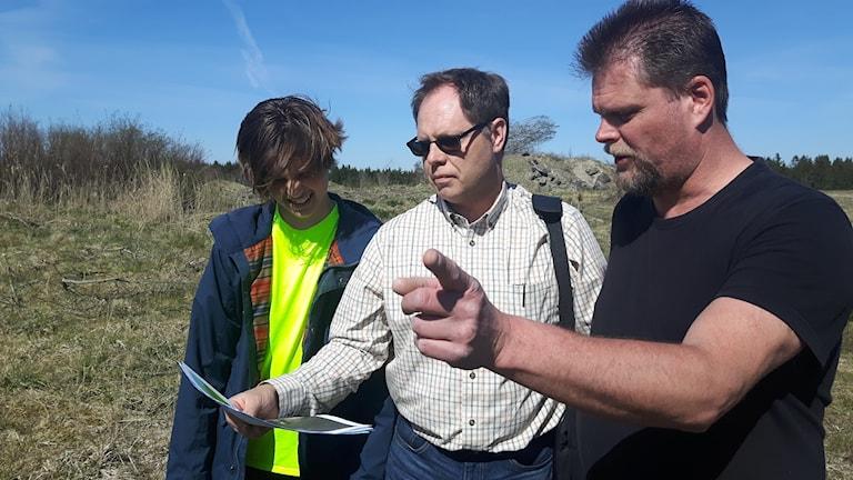 Tre män står och läser i ett papper. I bakgrunden soptippen