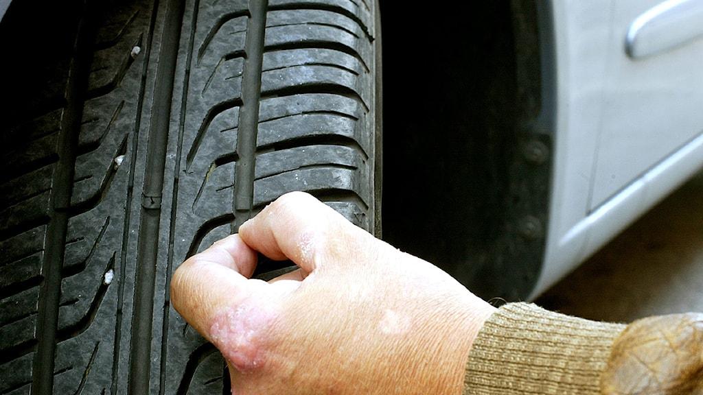 En man kontrollerar att bildäcket har rätt mönsterdjup. Foto: Pontus Lundahl/Scanpix.