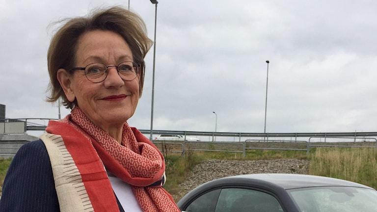 På bild syns Gudrun Schyman som står näst intill en bil. Det är dåligt väder, väldigt molnigt. Trots det dystra vädret ser vi inga dystra miner. För Gudrun, hon ler! Hon är för övrigt klädd i beige, rött och blått.