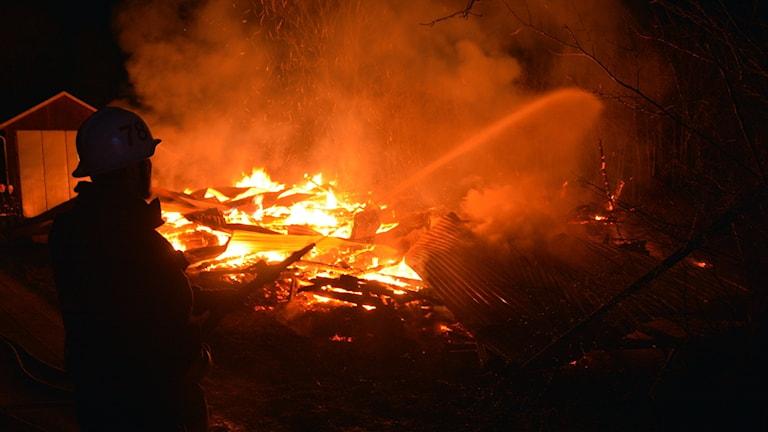 En byggnad brinner. Räddningstjänsten försöker släcka.