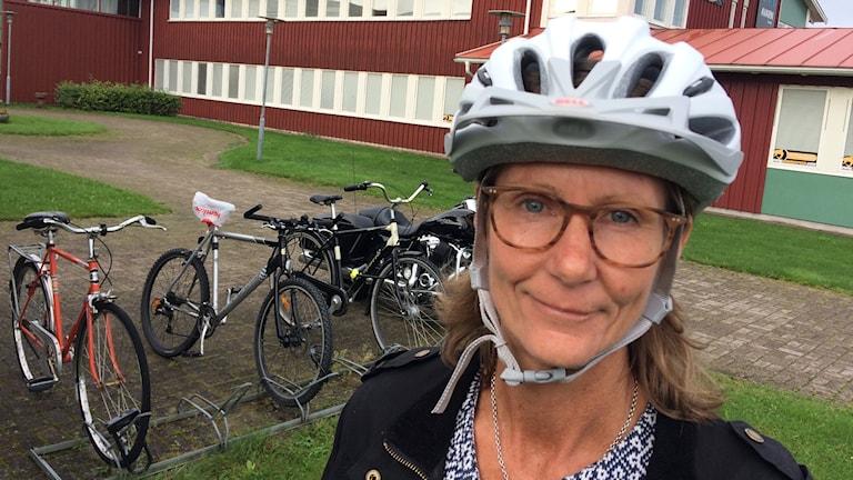 Porträtt av Agneta Berlin i cykelhjälm framför cyklar.