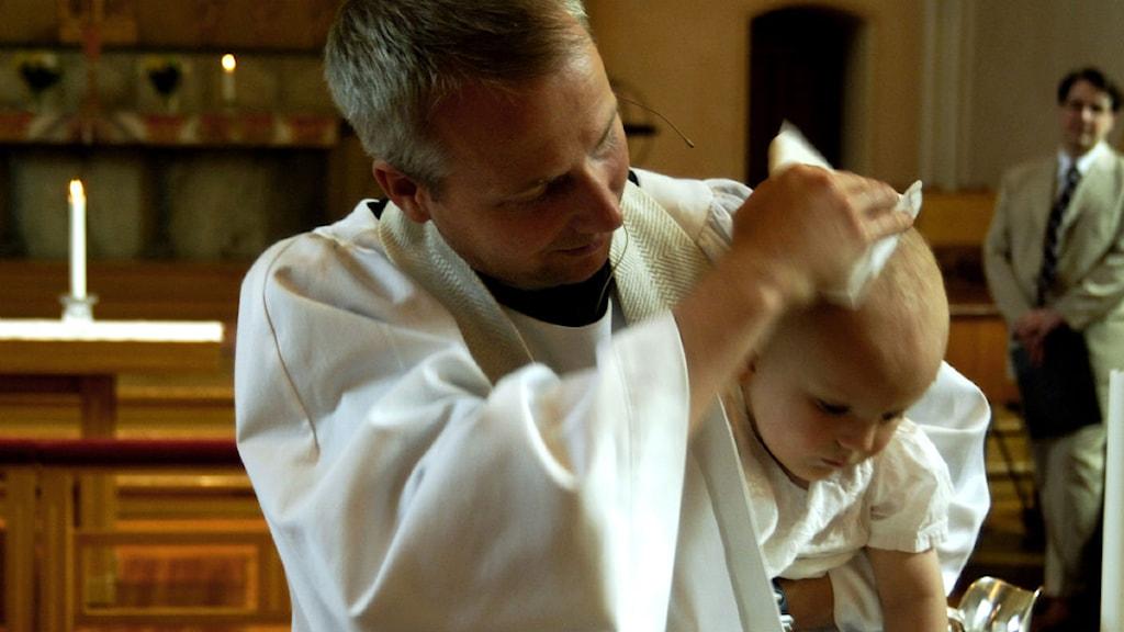 En präst döper en pojke. Foto: Hasse Holmberg/Scanpix