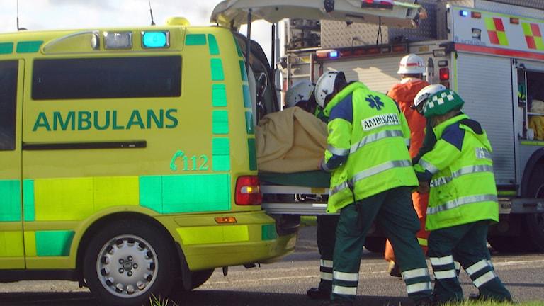 Räddningstjänst för en bår in i en ambulans. Foto: SVT Bild.