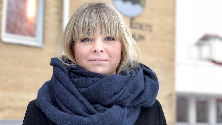 Julia Färjhage är blond, med lugg. Bärande en mörkblå sjal och en svart rock.