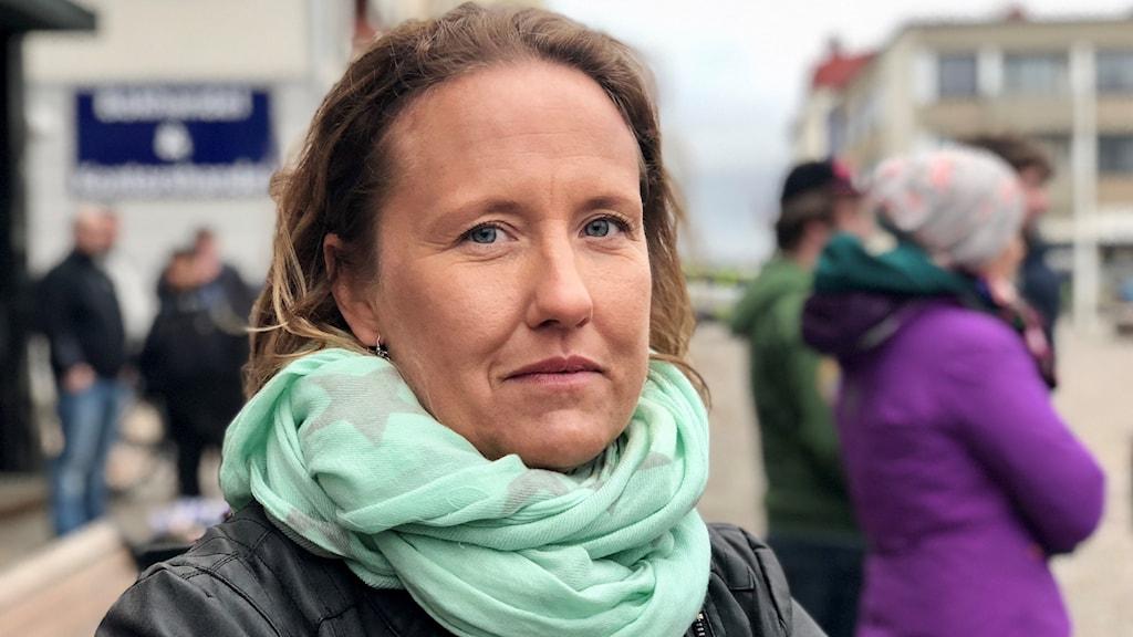 Viktoria Bertilsson, medelålderskvinna med brunt hår. Hon bär en turkos sjal. Står i en folkmassa på Kugnstorget i Lysekil.