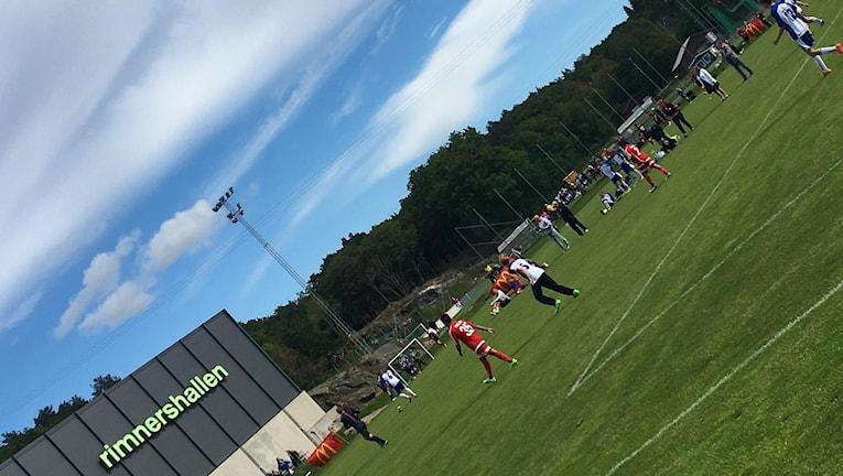 Bild på Rimnershallen och fotbollsspelare i förgrunden