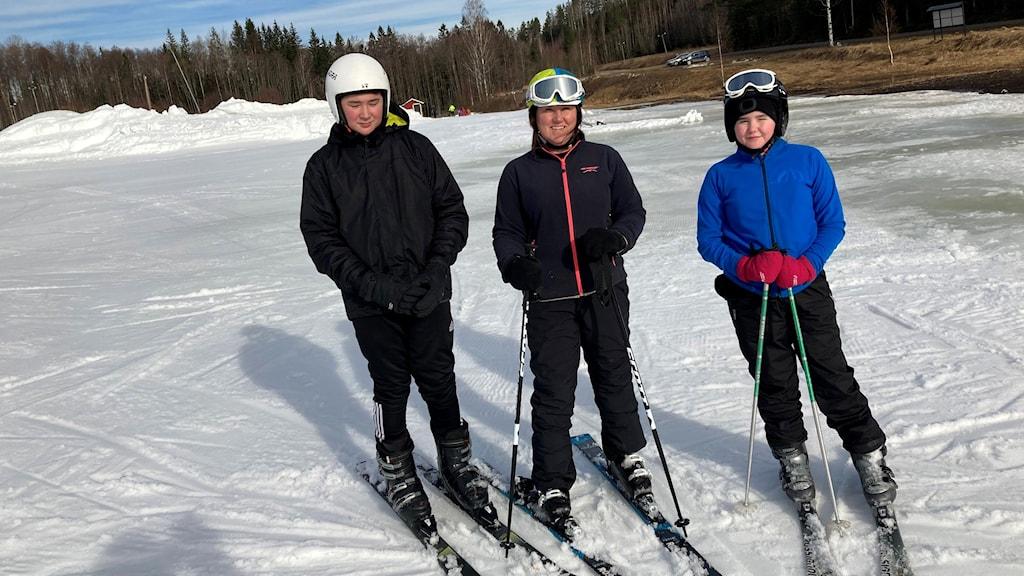 En familjebild med tre personer ute i snön.