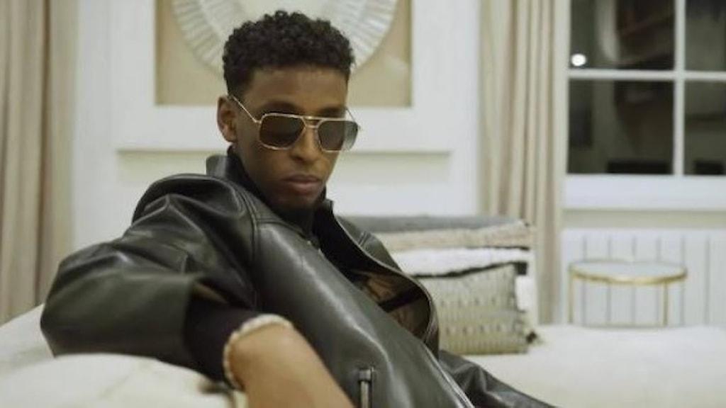 Yasin sitter i en soffa och tittar in i kameran. Han har solglasögon på sig.