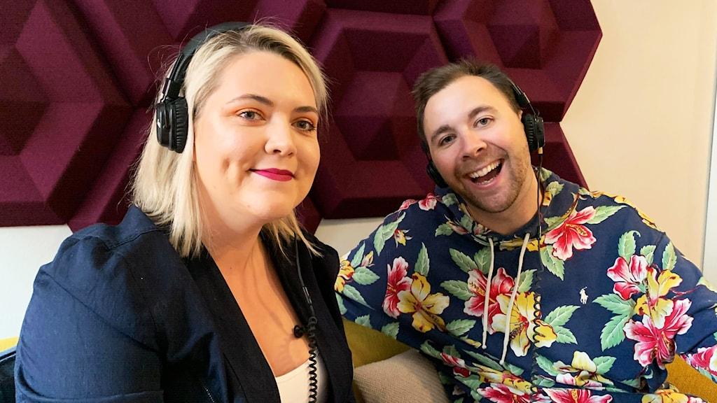 En kvinna och en man med hörlurar ler och tittar in i kameran.