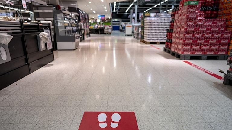 En skylt med texten Håll avstånd, i en matbutik.