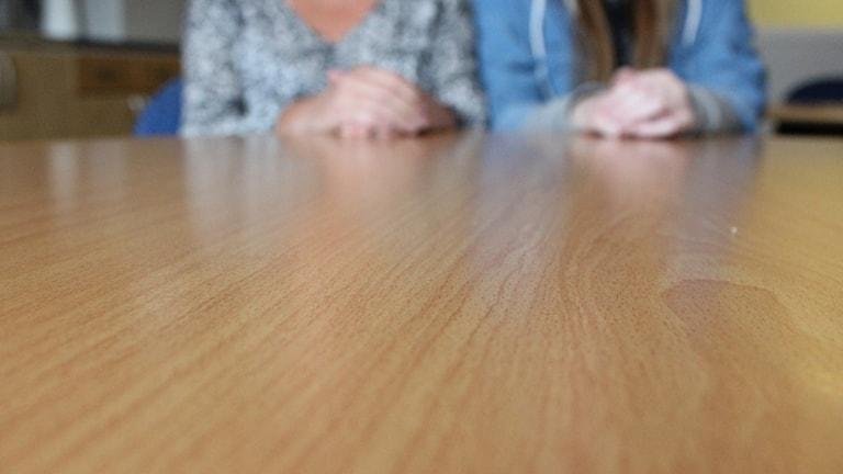 Bild på två personer som håller upp händerna på bordet
