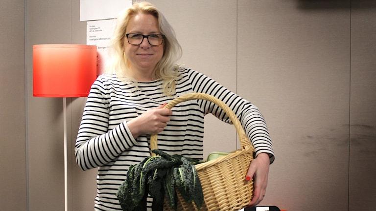 Karin Höberg håller en kort med svartkål i famnen. Foto: Julia Forsberg/Sveriges Radio
