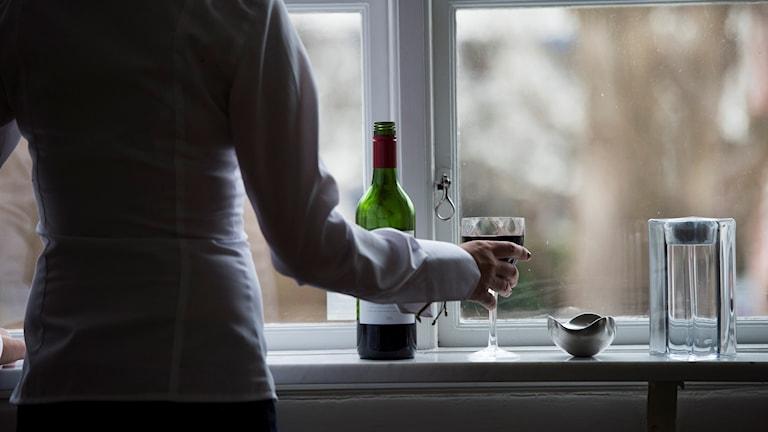 Silhuett av en kvinna som håller ett vinglas i handen. Foto: Fredrik Sandberg/TT