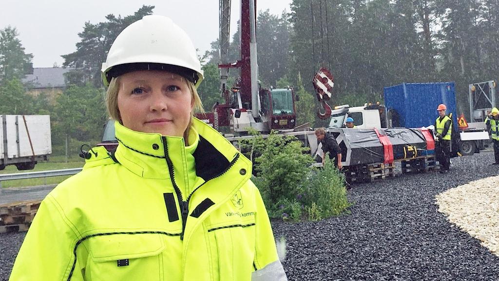 Projektledaren Marina Karlsson står framför en lastkran iförd reflexjacka och bygghjälm. Foto: Lars Sergård