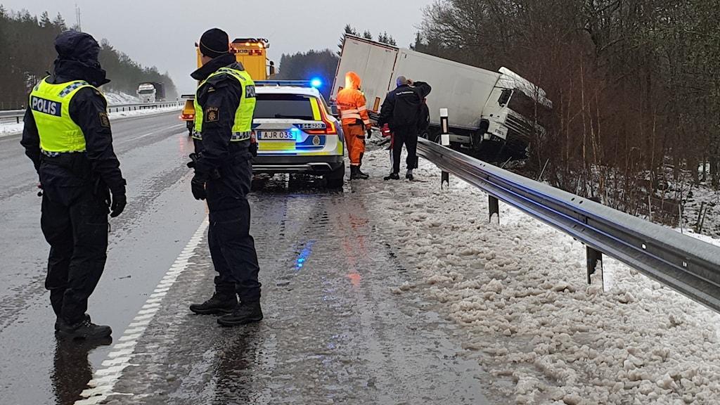 Bild från olycksplatsen, lastbil har kört av vägen. Poliser och polisbil.