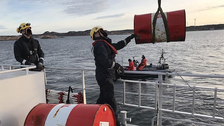Bild på Kustbevakningen som plockar upp två oljefat som hittats i Brofjorden.