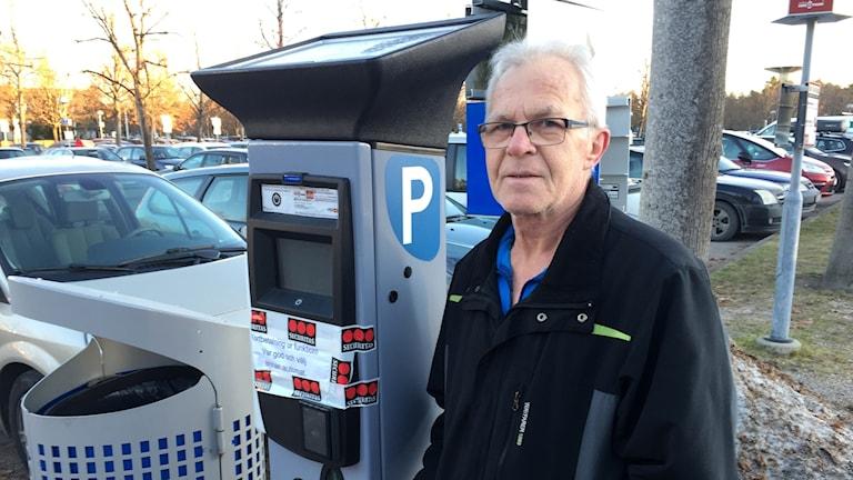 Kenneth Andersson från Trollhättan framför en trasig parkeringsautomat vid sjukhuset Näl. Foto: Richard Veldre/Sveriges Radio