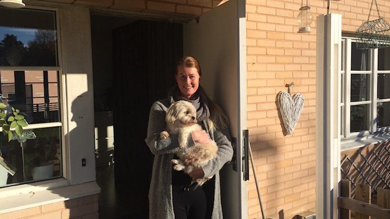 Karin Degrell med hunden Harry i famnen.