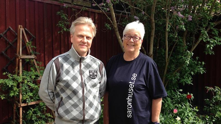 Man i grå tröja till vänster och kvinna i blå tröja t-shirt med texten saronhuset.se som står framför en rabatt