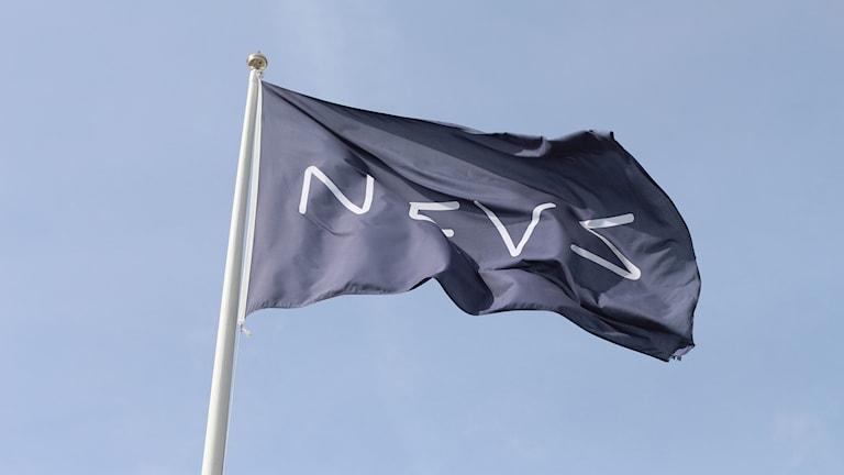 En flagga med Nevs logotyp på.