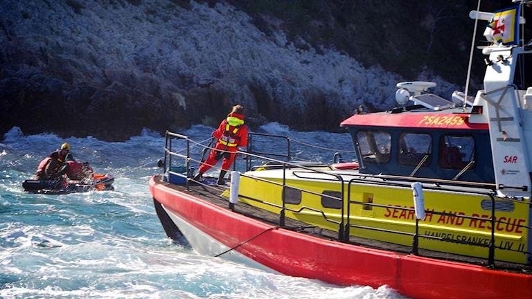 Här hjälper besättningen på en av de gula båtarna flyktingar i sjönöd.