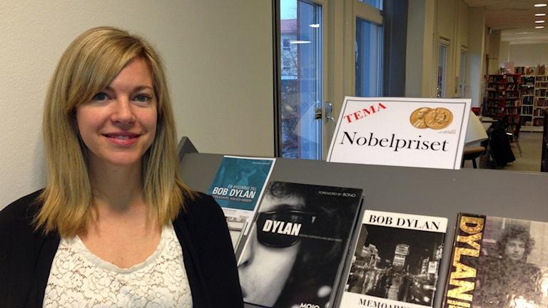 Louise Hallgren framför en bokhylla med böcker kring litteraturprisvinnaren Bob Dylan