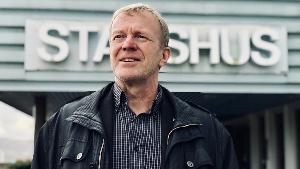 Oppositionsrådet Ingemar Samuelsson, tillika socialdemokrat, poserar framför kommunentrén i Uddevalla. Han är iklädd en skinnpaj, randig svart/vit skjorta. Han tittar bort och ler lite smått. Bakom hans huvud går att läsa: STADSHUS.