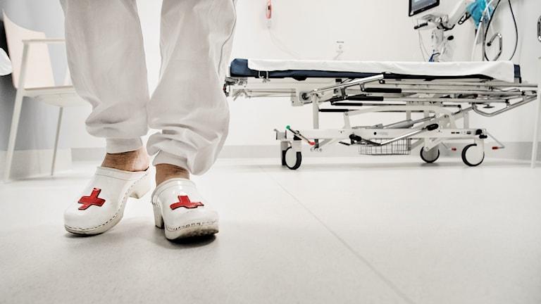 Golvet till ett sjukrum. På fotot syns ett par tofflor med röda korsets logga. I bakgrunden syns ett bår.