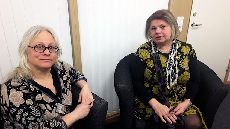 Två socialsekreterare sitter i ett litet samtalsrum i svarta fåtöljer.