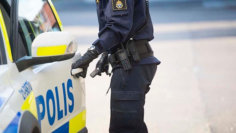 En polis öppnar dörren på en polisbil. Foto: Fredrik Sandberg/TT.