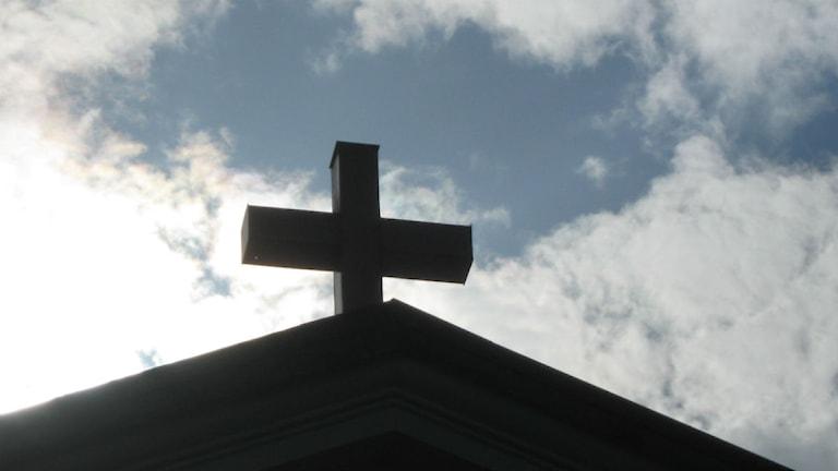 Bild på kyrkokors i motljus.