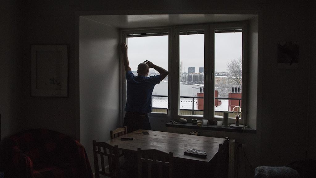 Man står i mörkt rum och tittar ut genom fönstret.