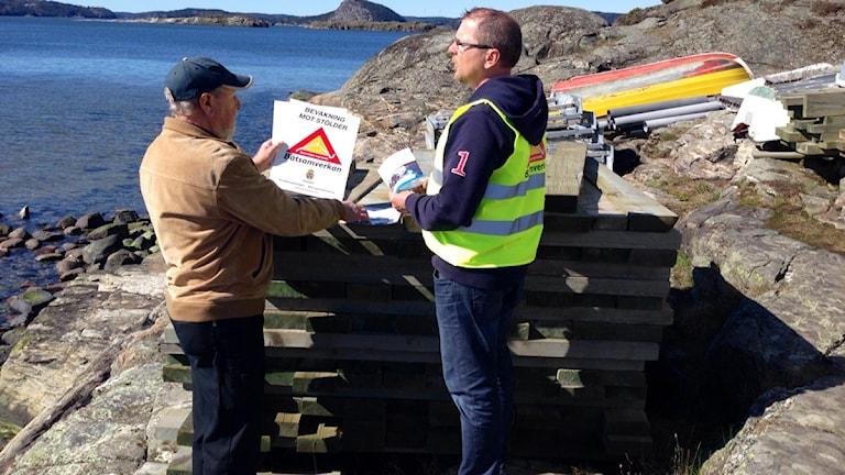 Polisen Thomas Andersson står tillsammans med båtägare Per-Olof Karlsson nere vid bryggan. Foto: Victor Jensen/Sveriges Radio.