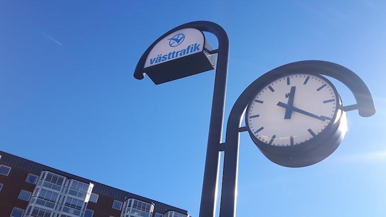 Västtrafik skylt och klocka Uddevalla Östra snett ovanifrån. Himlen är blå och solen blänker mot klockan.