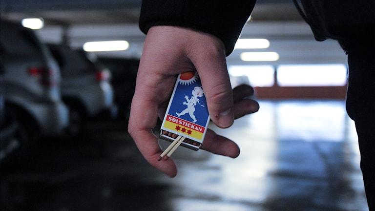 Närbild på en hand som håller i tändstickor, i garagemiljö.