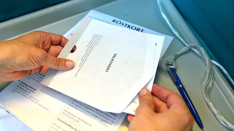 En person stoppar en valsedel i ett kuvert i en röstlokal. Foto: Henrik Montgomery/TT.