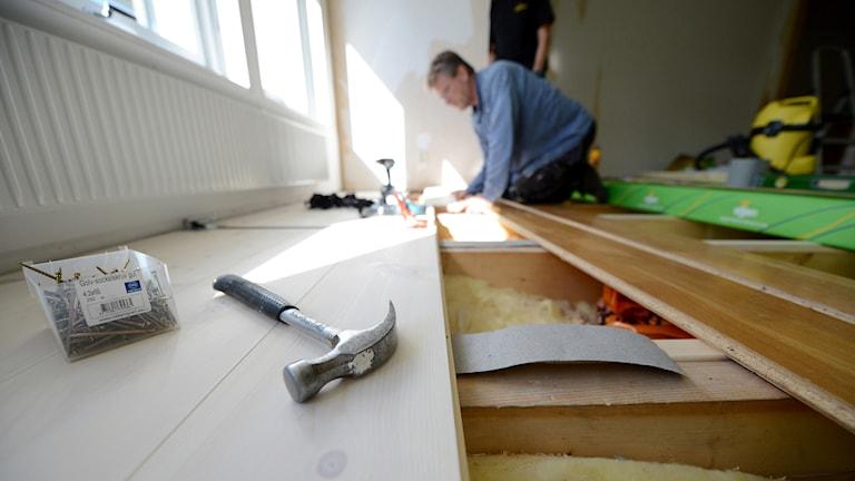 En snickare lägger ett trägolv i en villa. Under golvet syns husets isolering. Foto: Fredrik Sandberg/TT.