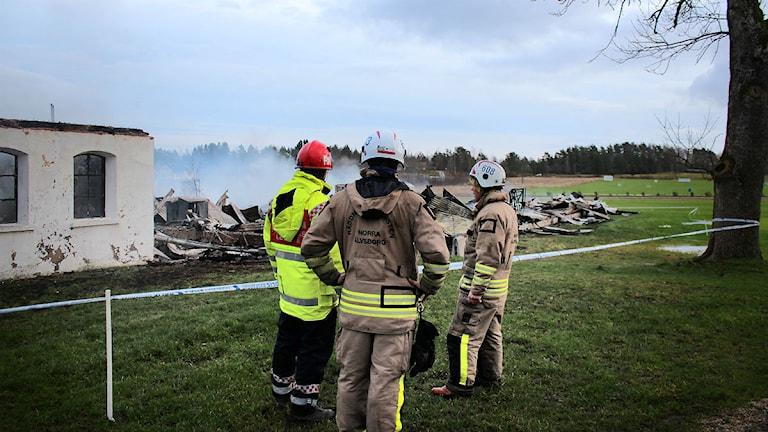 Brandmännen Robert Korosec, Tobias Coster och Sven Eriksson blickar ut över förödelsen efter branden. Mellerud Foto: Tommy Öster / Sveriges Radio P4 Väst