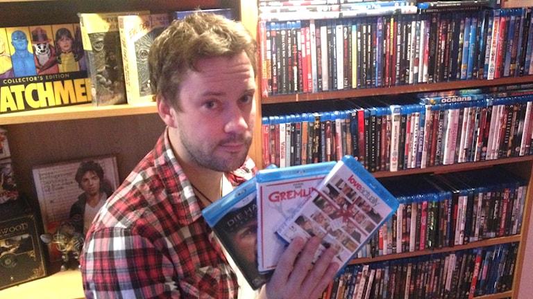 Bild på Magnus Sörensen hållandes tre DVD-filmer. Foto: Jimmie Schewenius/Sveriges Radio